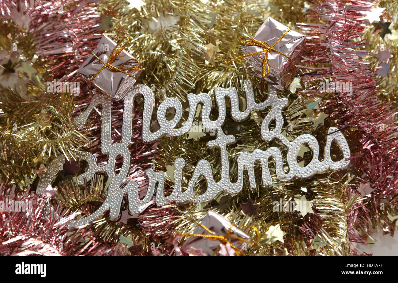 Merry Christmas on pink and golden tinsel - Stock Image