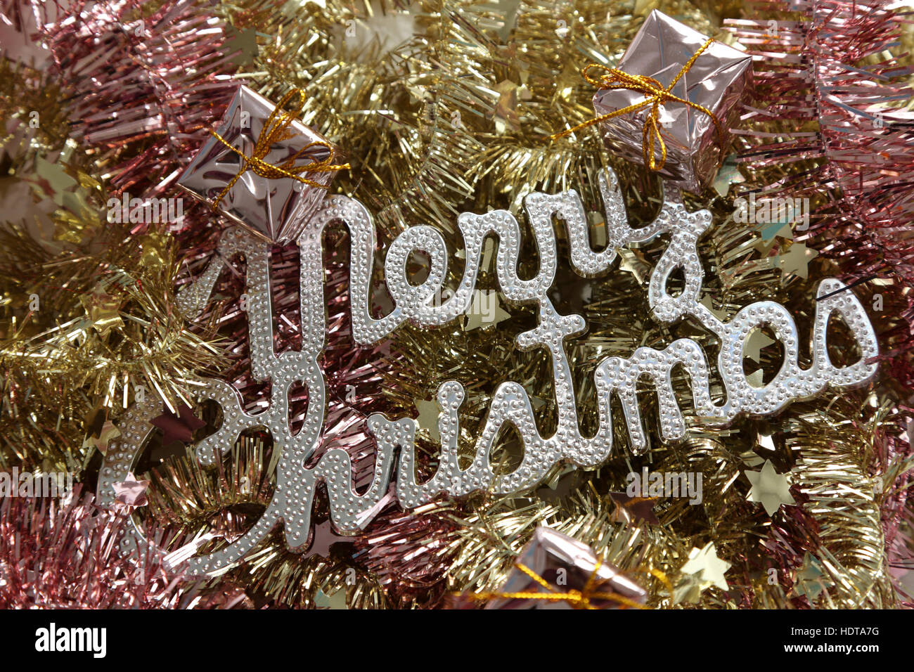 Merry Christmas on golden and pink tinsel - Stock Image
