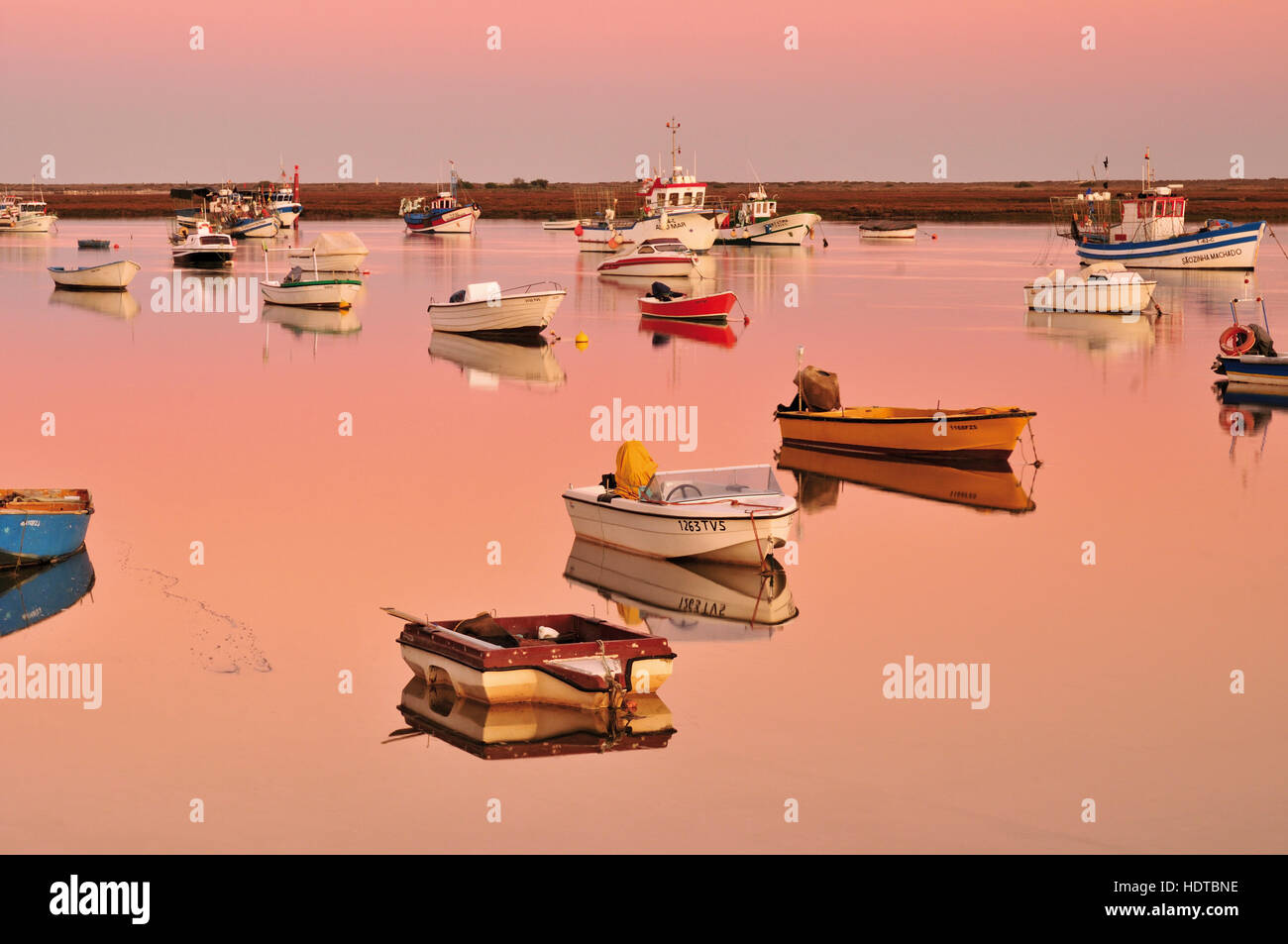 Fisher boats anchoring in the calm waters of lagoon Ria Formosa at twilight - Stock Image