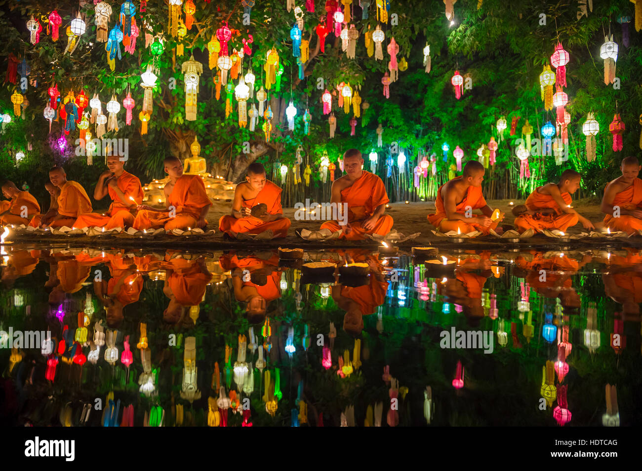 CHIANG MAI, THAILAND - NOVEMBER 06, 2014: Young Buddhist monks sit meditating at a festival of lights loi krathong - Stock Image