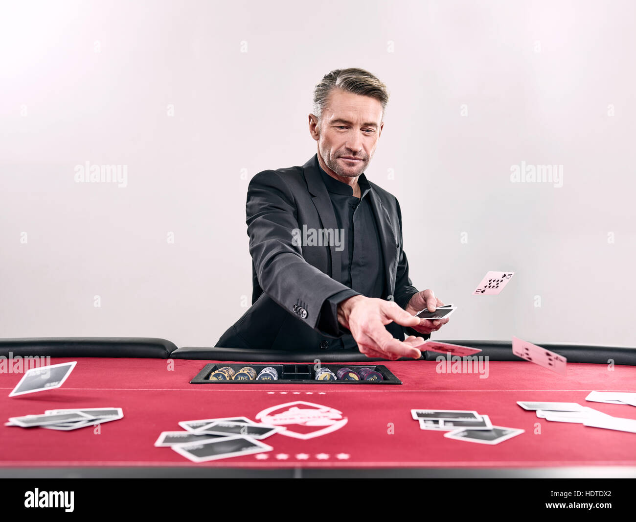 Man distributing playing cards, blackjack, casino, chips - Stock Image