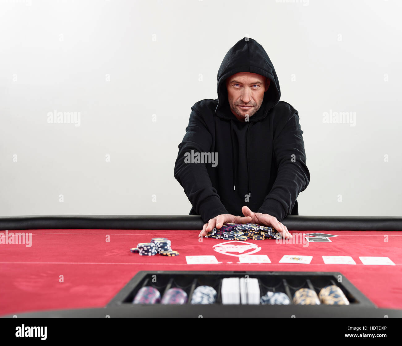 Man in hooded sweater going all-in, chips, blackjack, casino - Stock Image