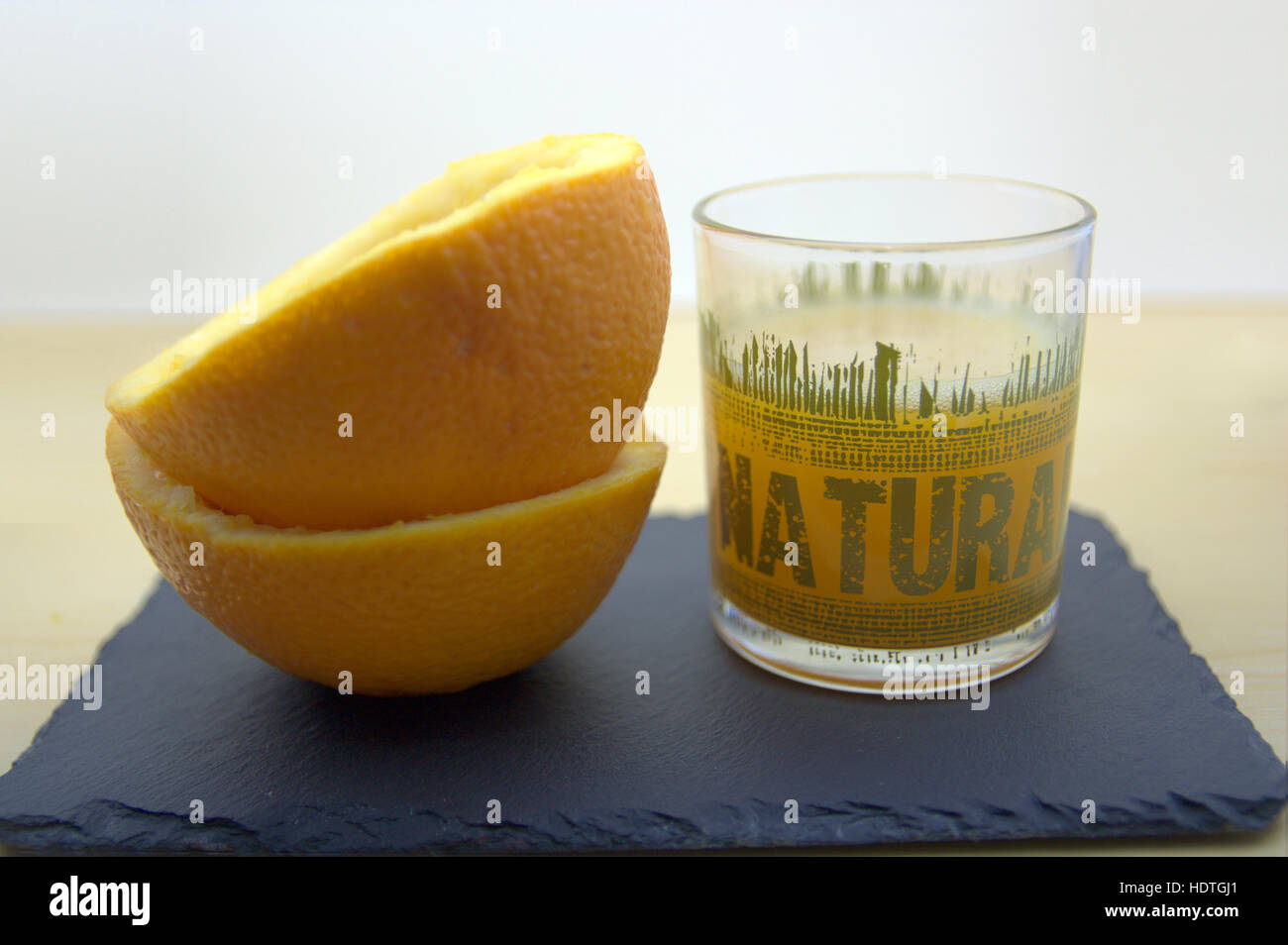 A tall glass of orange juice with oranges around. - Stock Image