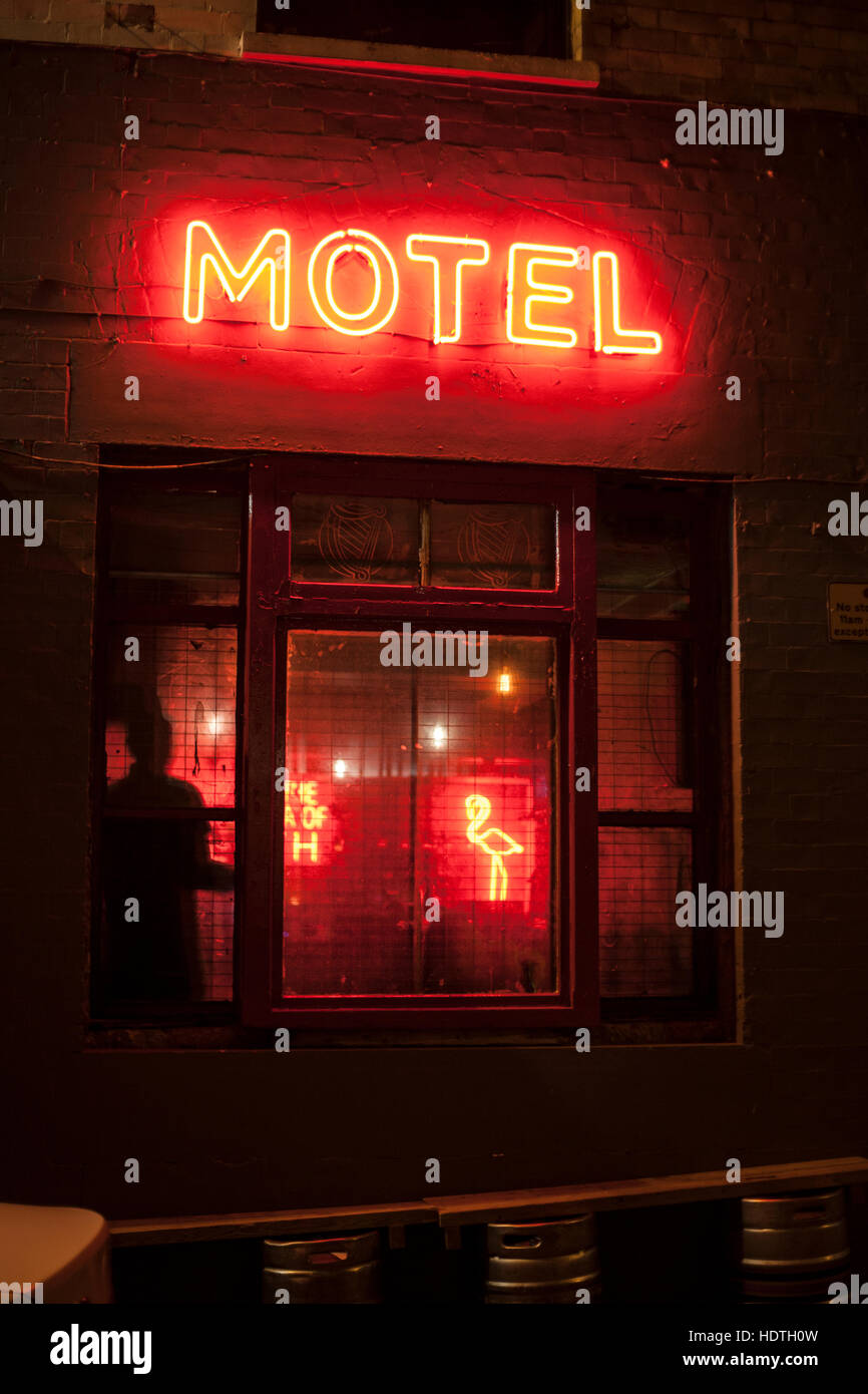 Shadow and neon flamingo through the window, under a neon motel sign. - Stock Image