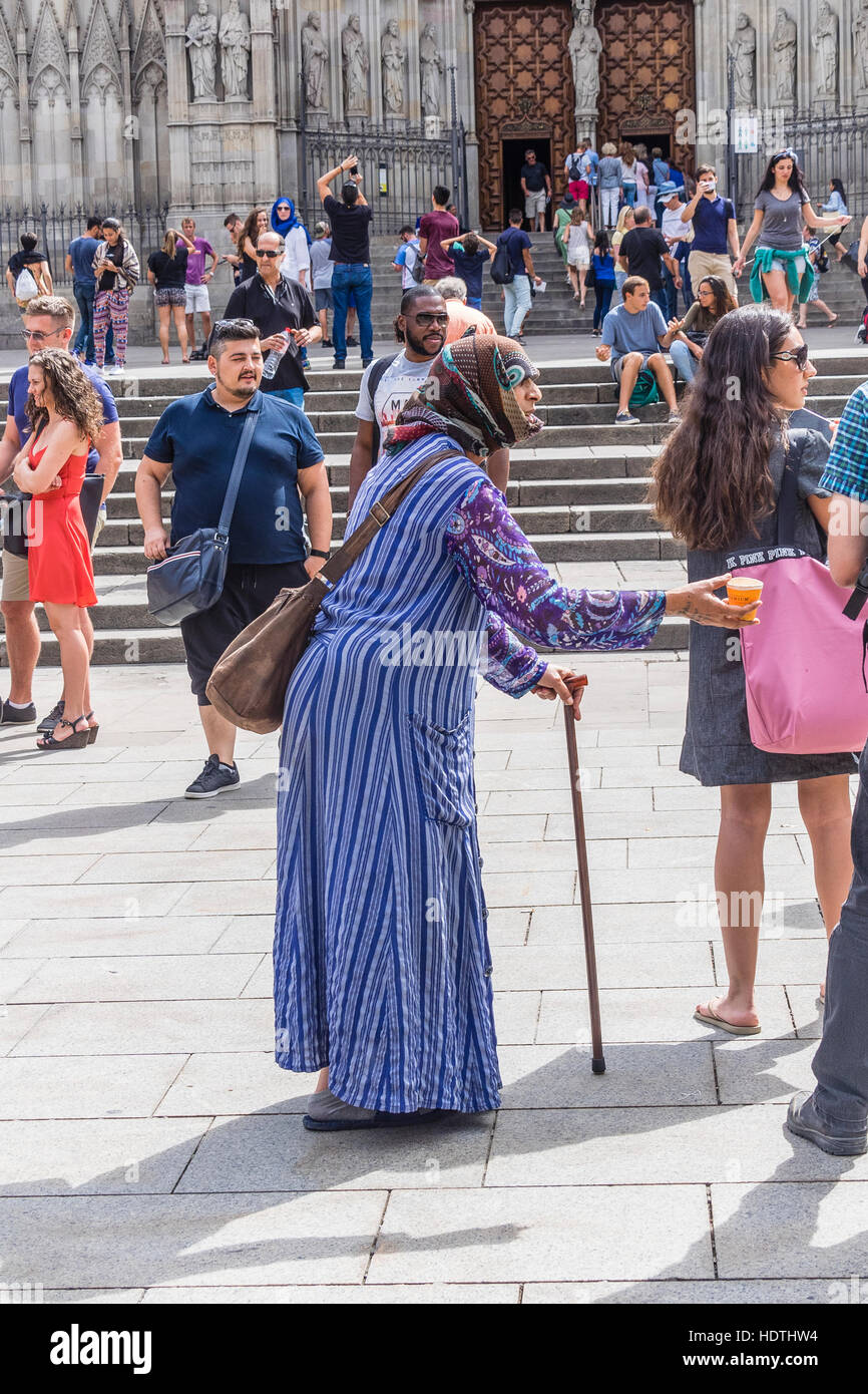 Muslim older woman beggar dressed in a burka begging in a plaza in Barcelona, Spain - Stock Image