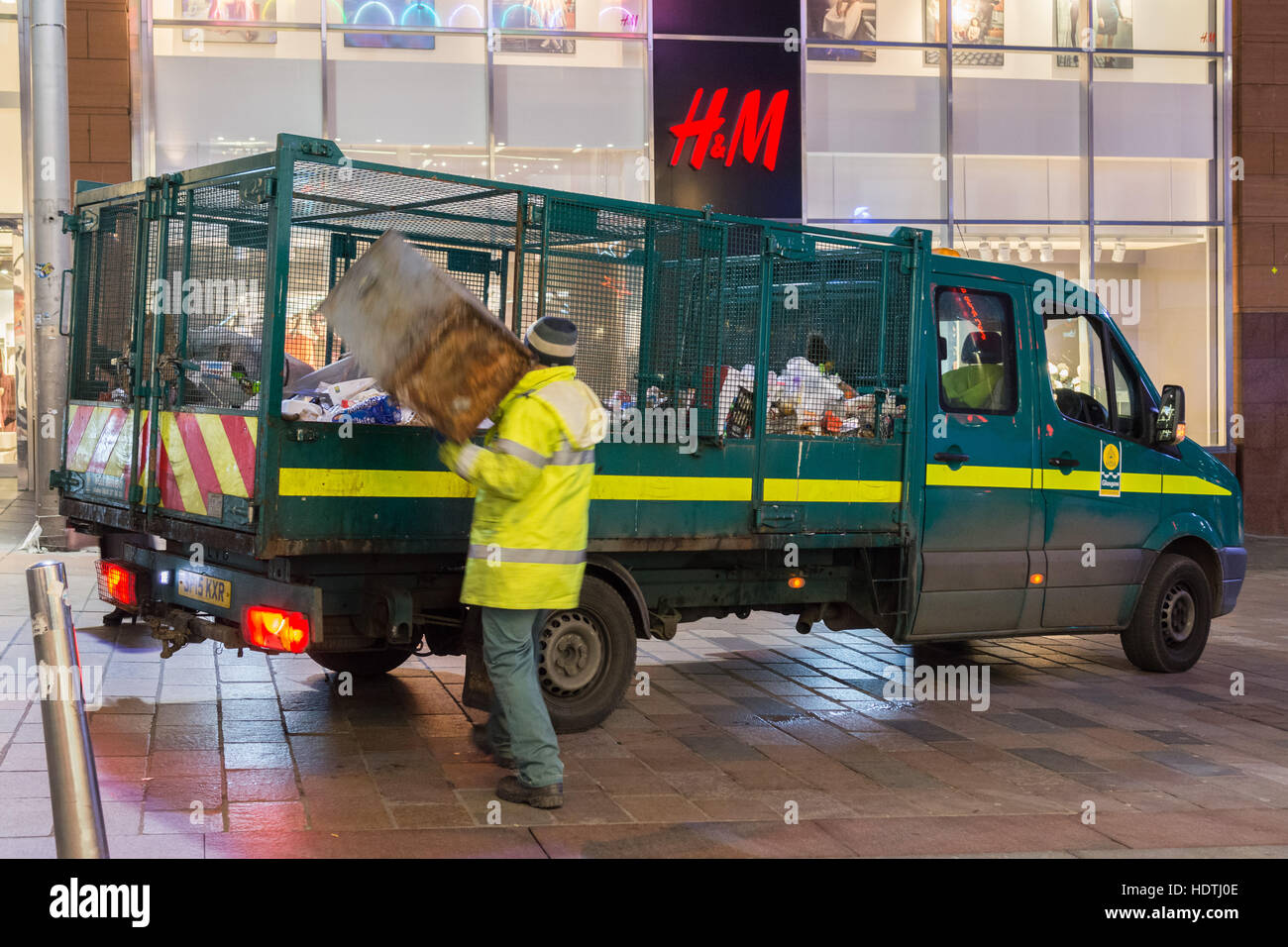council worker emptying litter bins in Glasgow city centre at night - Stock Image