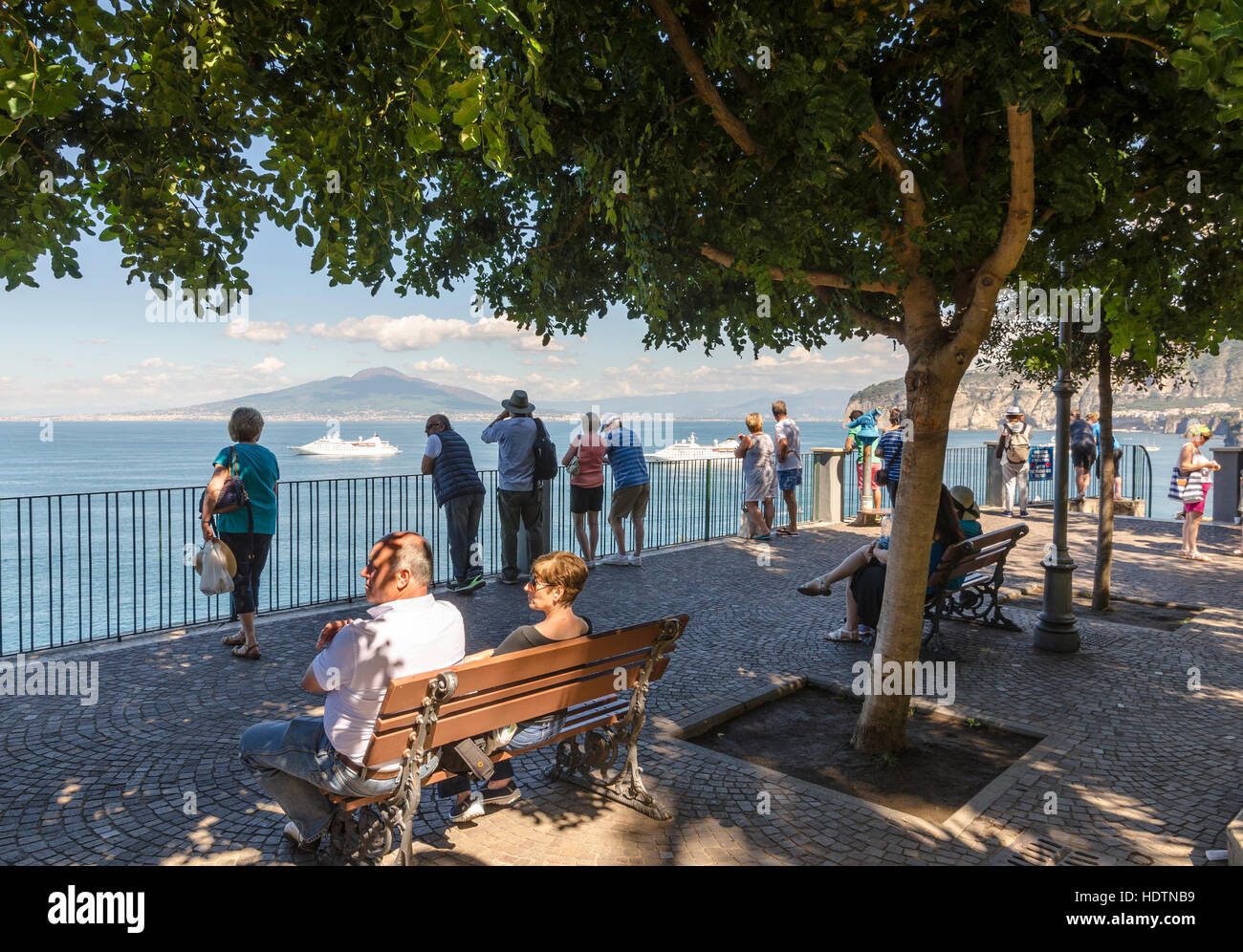 Tourists at the sea front in Villa Comunale Park Sorrento looking at the Gulf of Naples with Mount Vesuvius in the - Stock Image