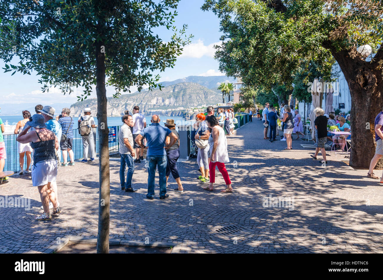 Tourists at the sea front in Villa Comunale Park, Sorrento, Italy, looking at the Gulf of Naples - Stock Image