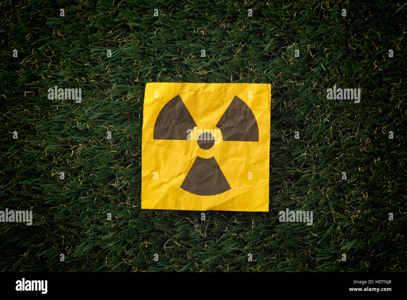 Radiation warning sign on a green grass. Close up. - Stock Image