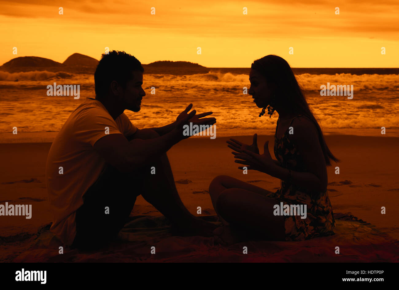 Love couple with relationship difficulties outdoor at beach at sunset - Stock Image