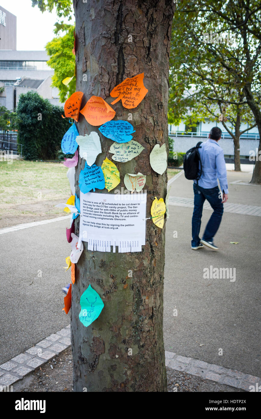 Notice to sign a petition against the Garden Bridge pinned to a tree at risk of removal, Southbank, London, UK - Stock Image