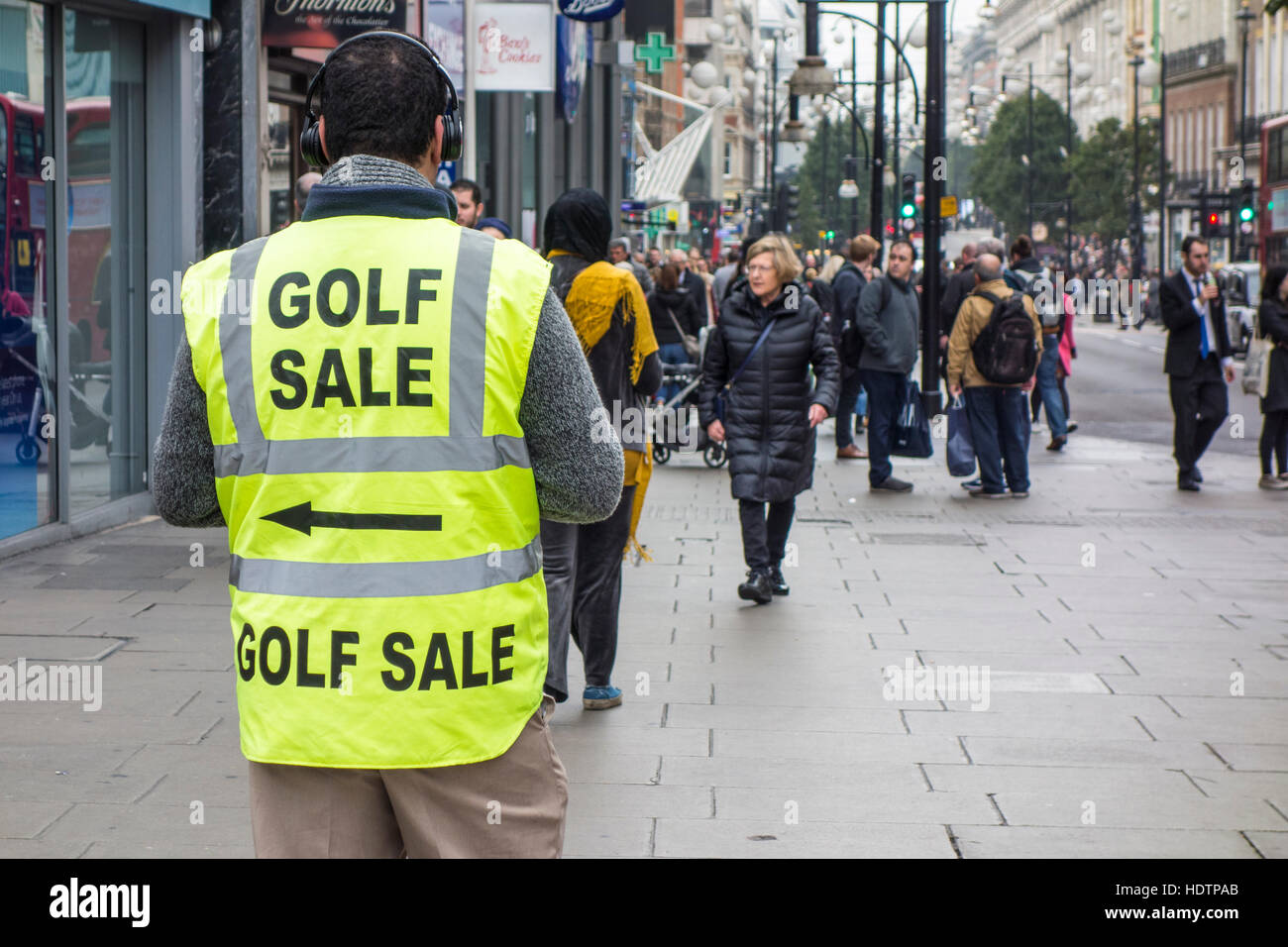 Shoppers passing man wearing high visibility jacket with Golf Sale advertising sign. Oxford Street, London - Stock Image
