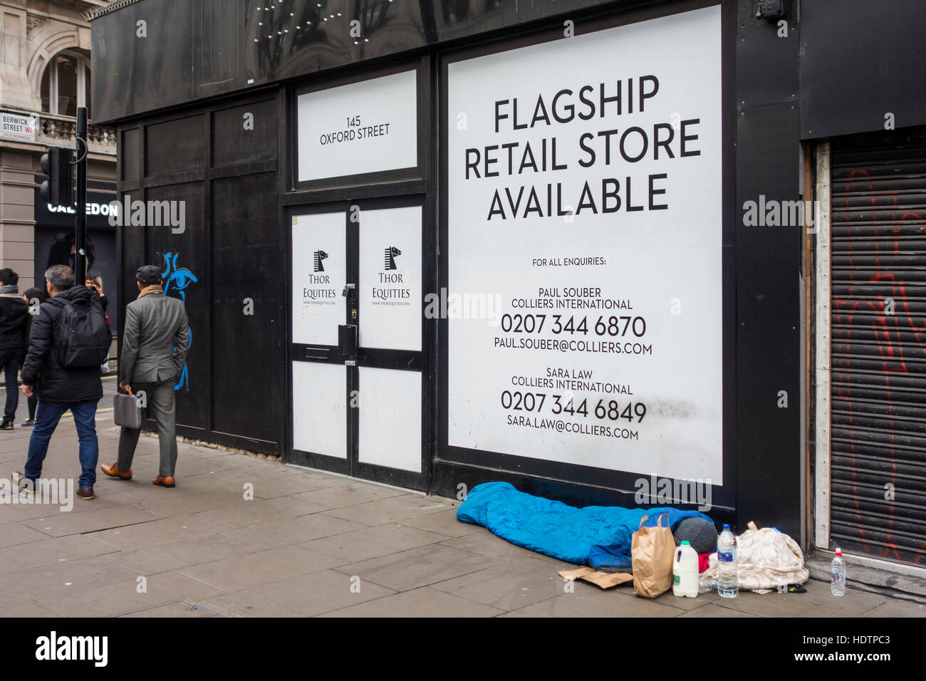 Homeless person sleeping outside an empty retail unit on Oxford Street in London, UK - Stock Image