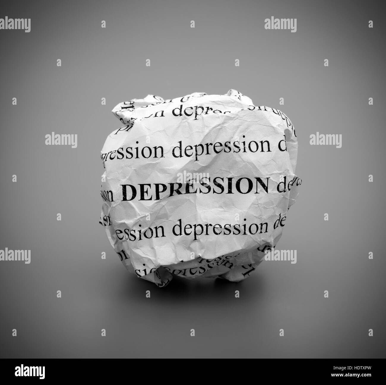 Crumpled paper ball with words Depression on gray background. Black and white. - Stock Image