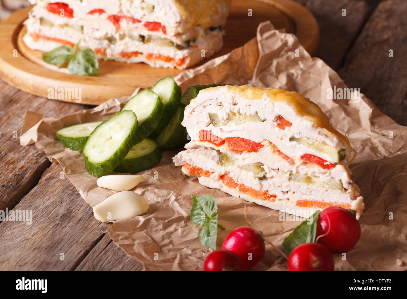 Piece Chicken casserole with vegetables and cheese on paper. horizontal - Stock Image