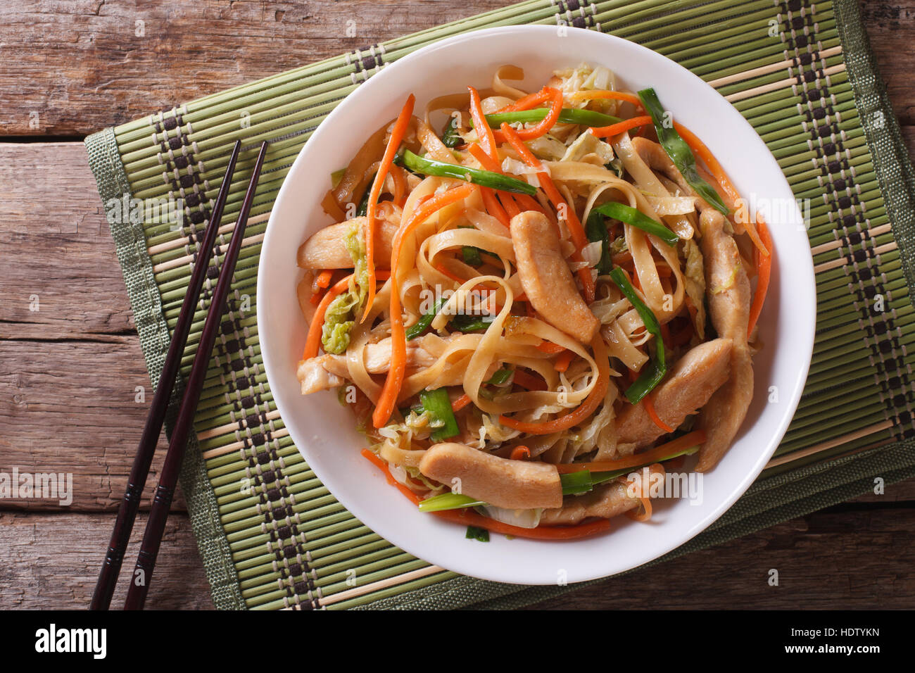 Chow Mein: fried noodles with chicken and vegetables close-up. horizontal view from above - Stock Image