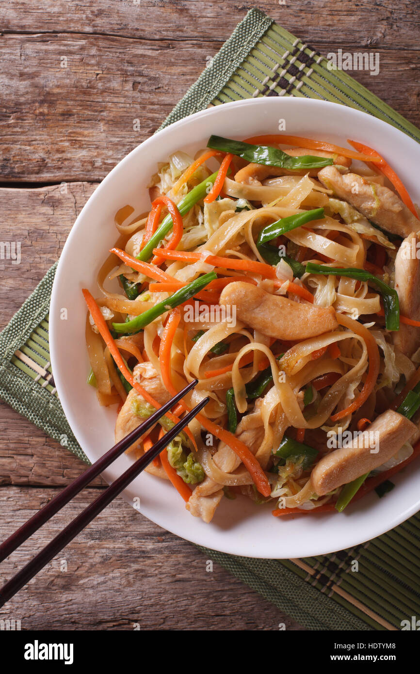 Chow Mein: fried noodles with chicken and vegetables close-up. vertical top view - Stock Image