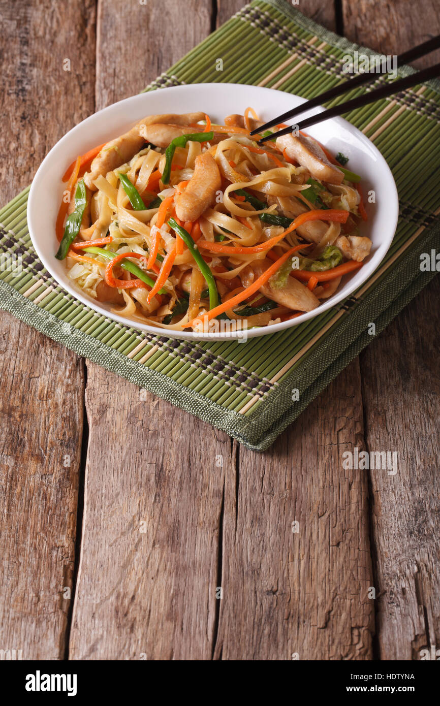 Chow mein with chicken and vegetables on the table. vertical - Stock Image