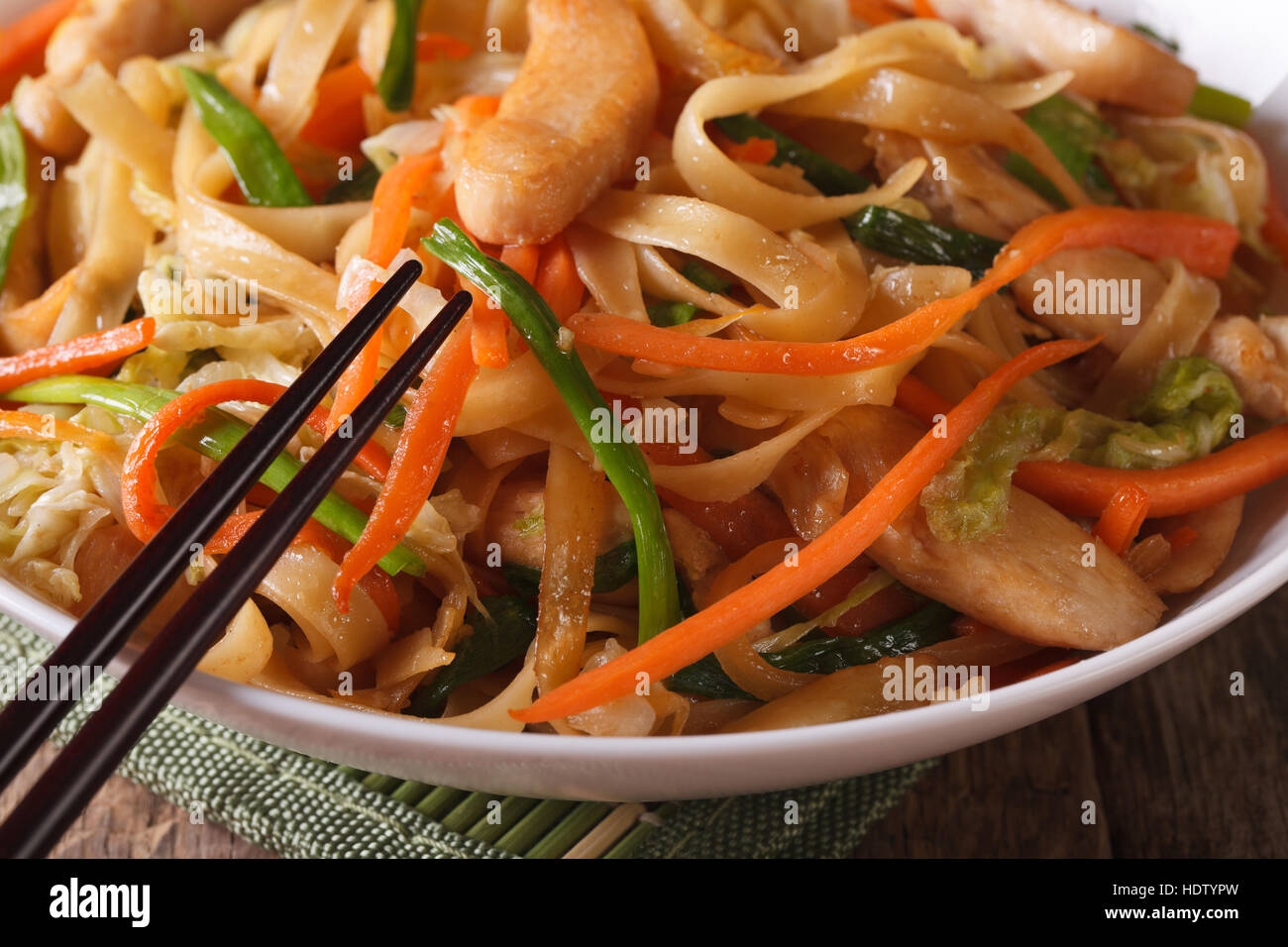 Chinese food: fried noodles with chicken and vegetables macro. horizontal - Stock Image