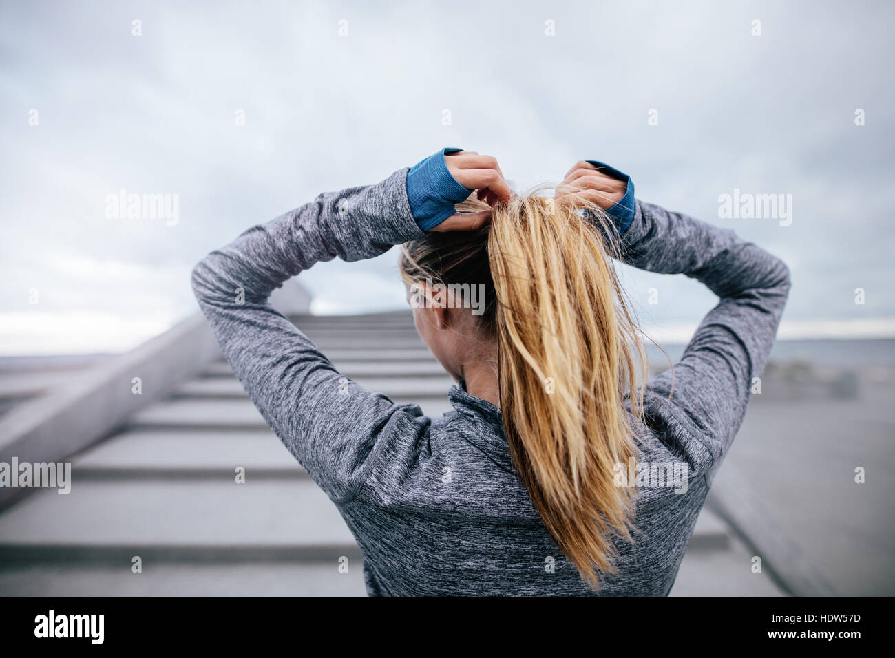 Rear view shot of fit female athlete tying hair before her workout. Young woman getting ready for training. - Stock Image