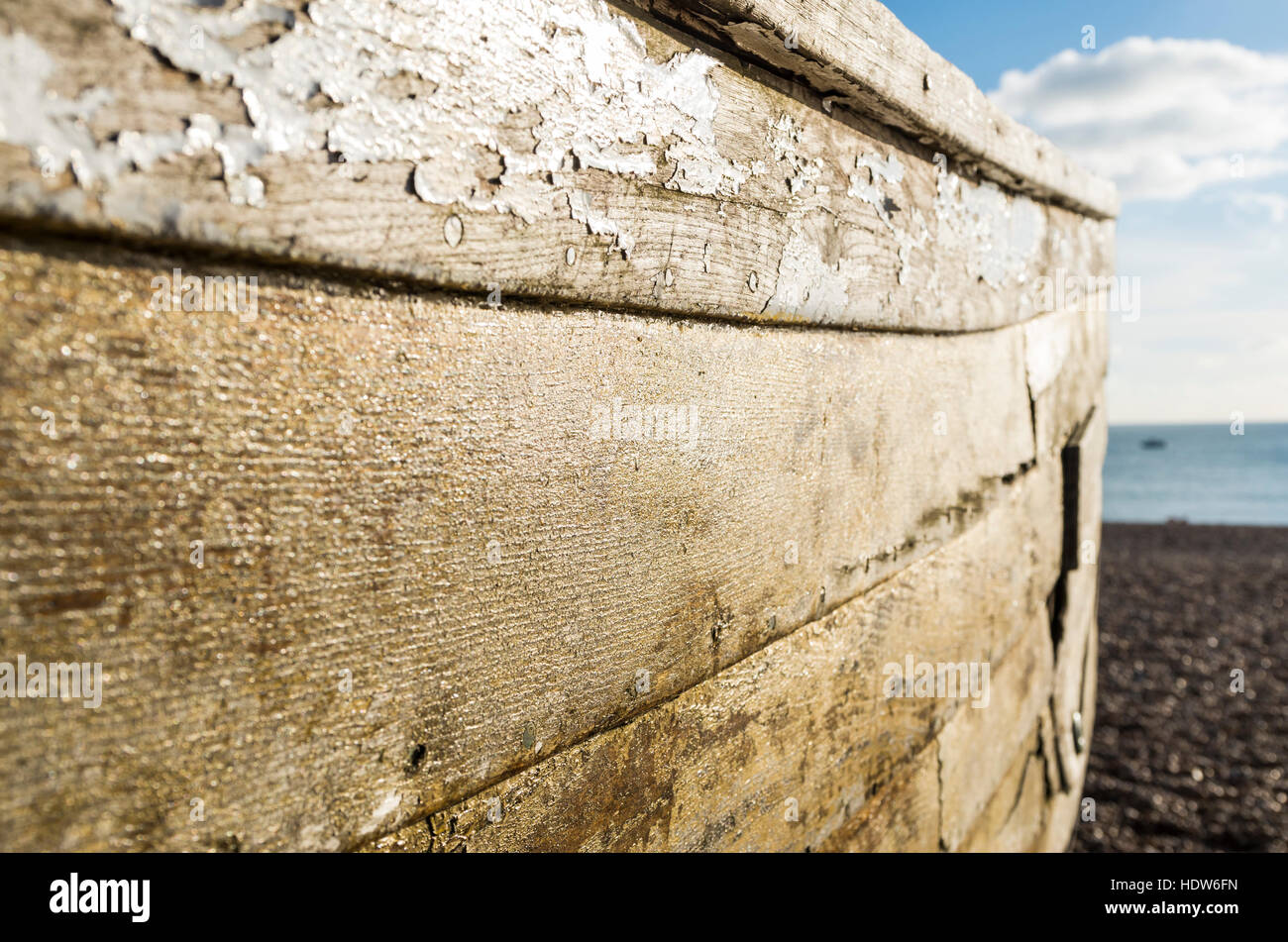 View along the side of a decaying old derelict wooden fishing rowing boat moored on the beach - Stock Image