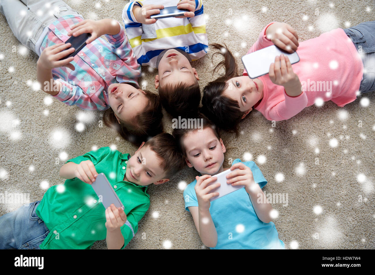 children with smartphones lying on floor - Stock Image