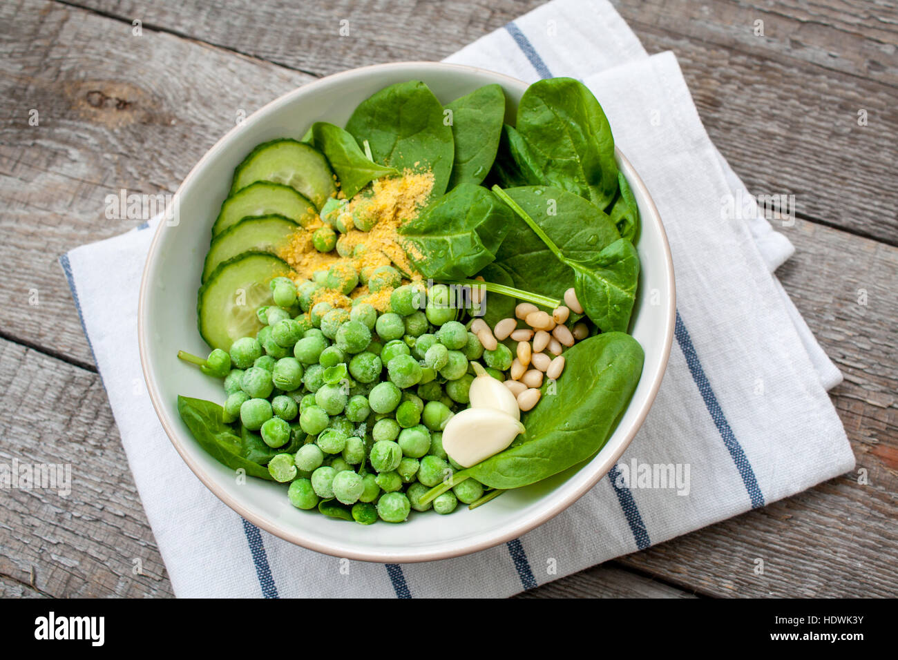 Ingredients for Green peas spinach basil pesto in a white bowl on a wooden background. Love for a healthy raw food - Stock Image