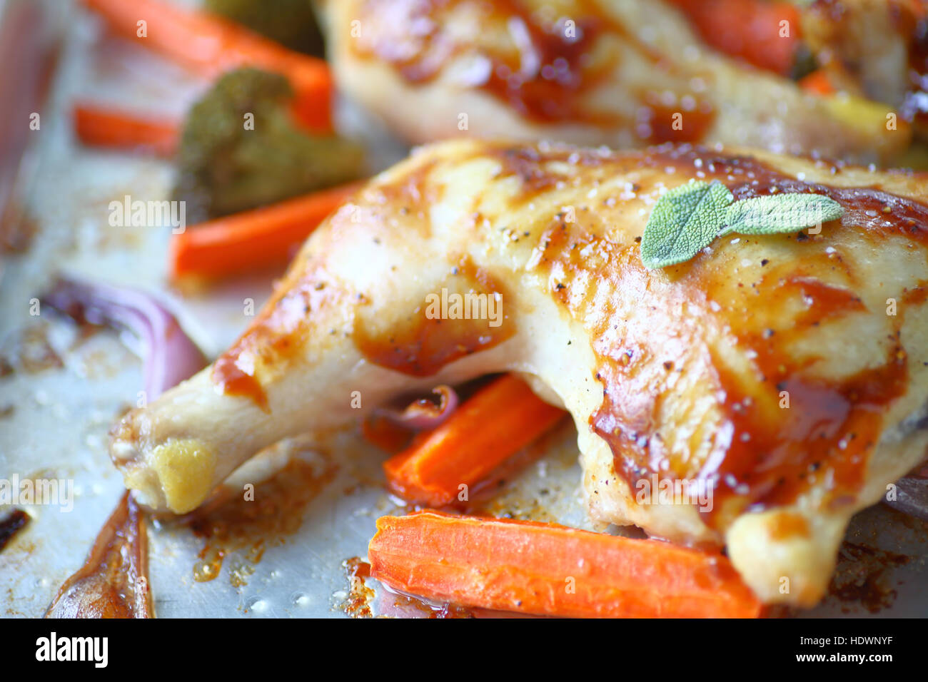 Roast chicken with fresh sage leaves, carrots, broccoli and onions on a sheet pan - Stock Image