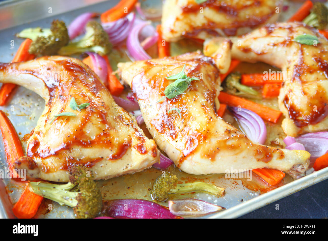 Chicken quarters roasted with carrots, onions and broccoli on sheet pan - Stock Image