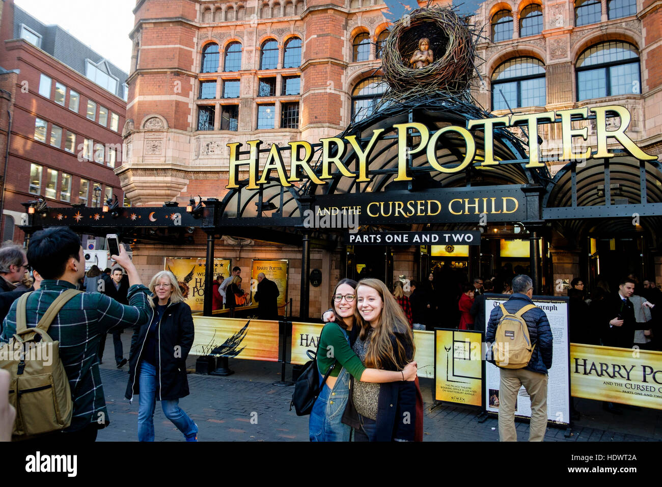 Visitors to London pose for photographs in front of Harry Potter and The Cursed Child at the Palace Theatre, London, - Stock Image