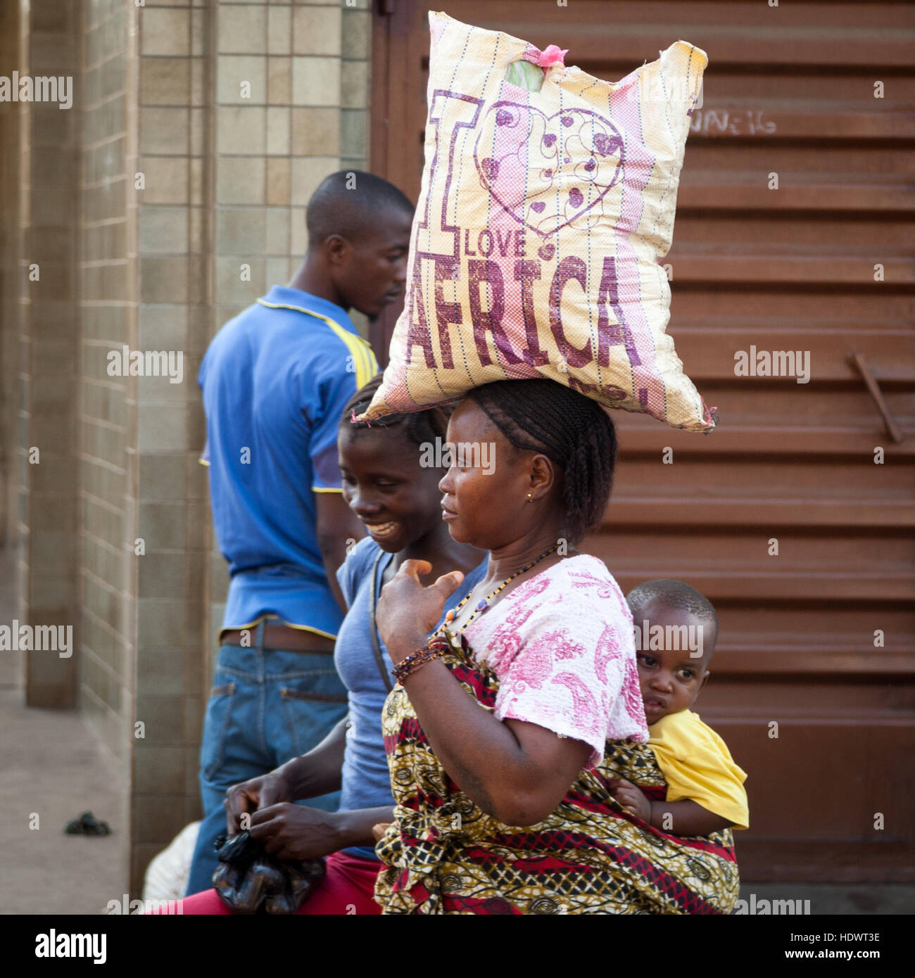 """""""I love Africa"""" - Woman carrying bag with inscription on her head and baby on her back Stock Photo"""