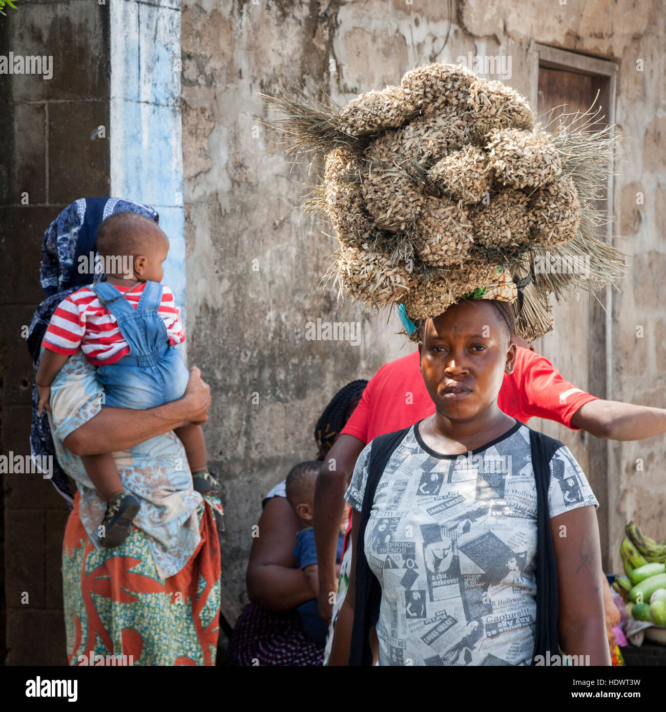 African woman carrying brooms on head Stock Photo