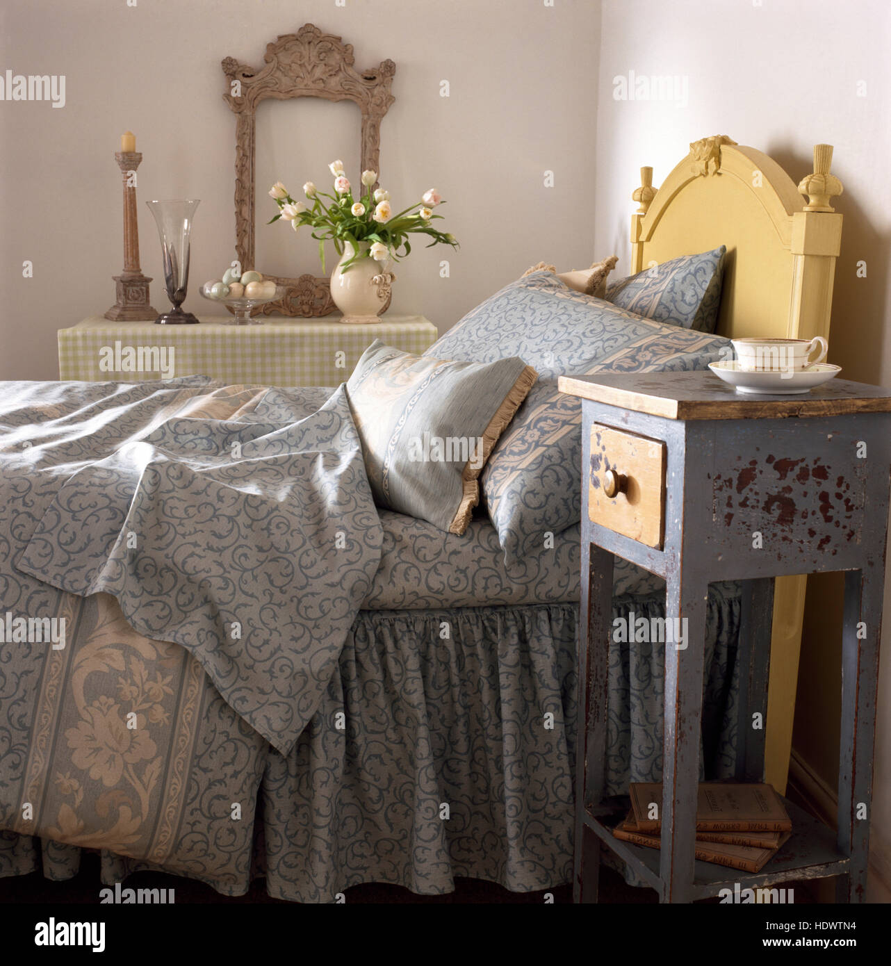 Small distressed painted bedside table beside bed with a pale gray patterned duvet and pillows in an economy style - Stock Image