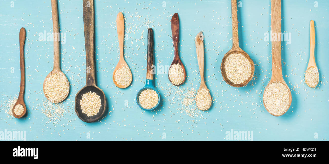 Quinoa seeds in different spoons over blue background - Stock Image