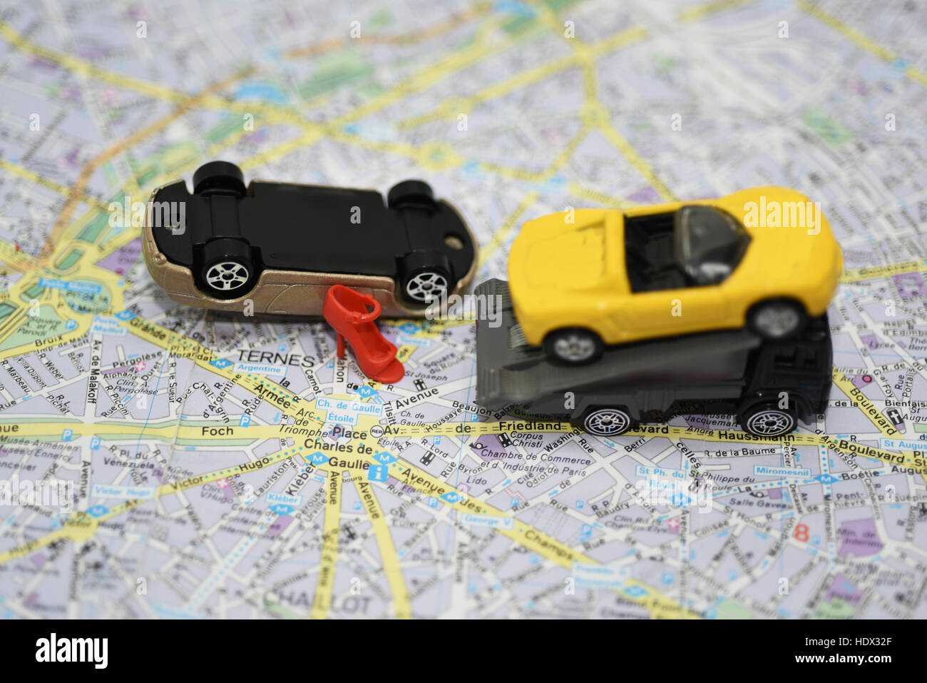 Abstract composition on the road accident. Paper map with small toy ...