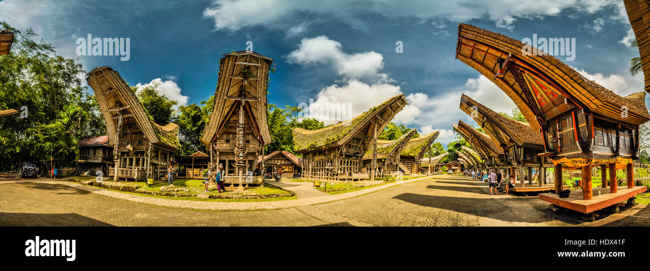 Panoramic photo of tongkonans with saddleback roofs and small square in Kete Kesu, Toraja region in Sulawesi, Indonesia. - Stock Image