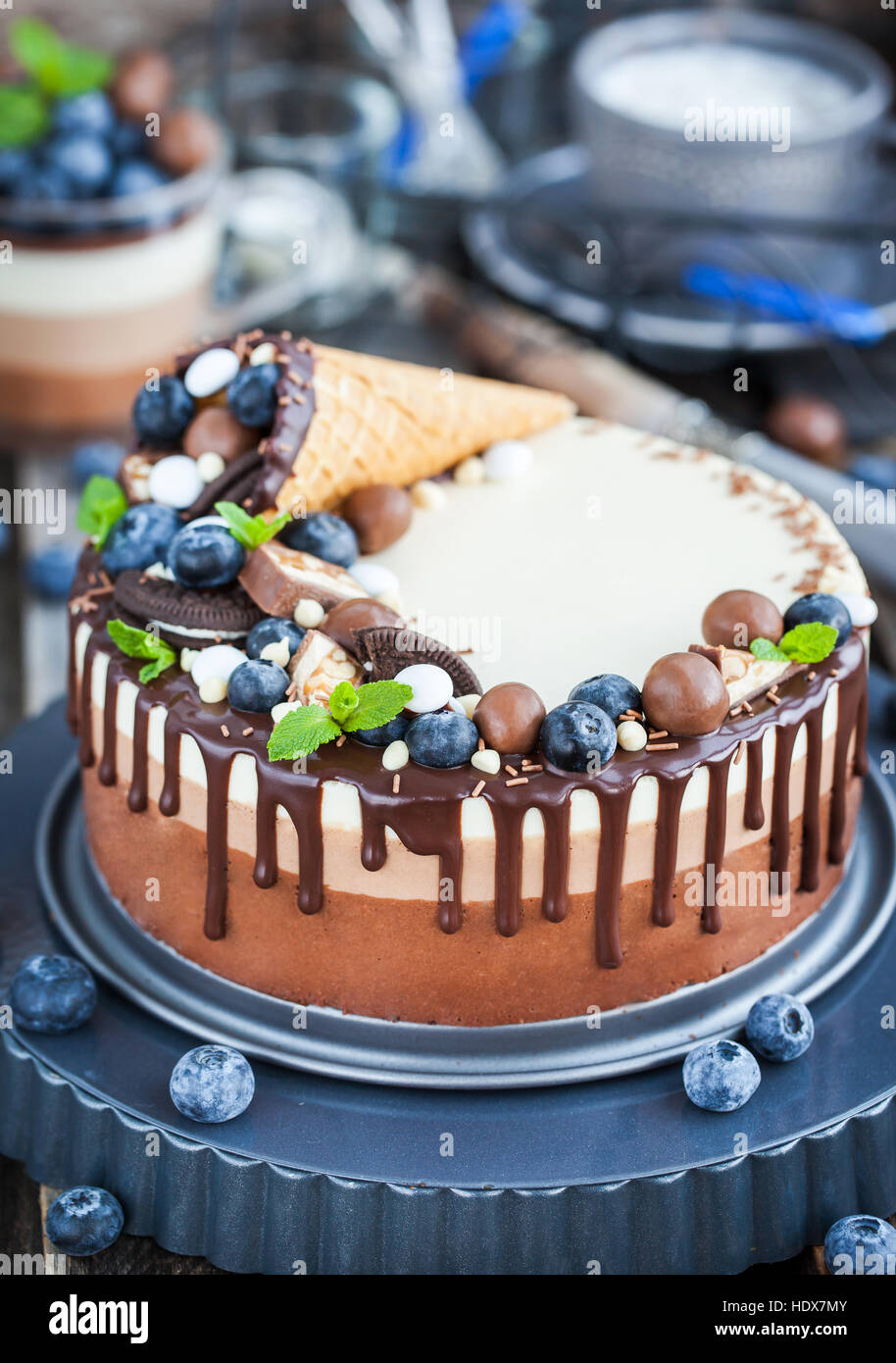 Delicious three chocolate mousse cake decorated with waffle cone, fresh blueberry, mint, candies and frosting Stock Photo