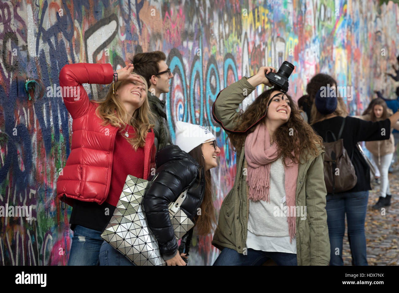 Young visitors pose in front of the John Lennon Wall, in Malá Strana, Prague - Stock Image