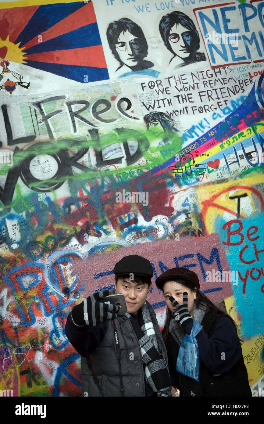 Two visitors pose for a selfie in front of the John Lennon Wall, in Malá Strana, Prague - Stock Image