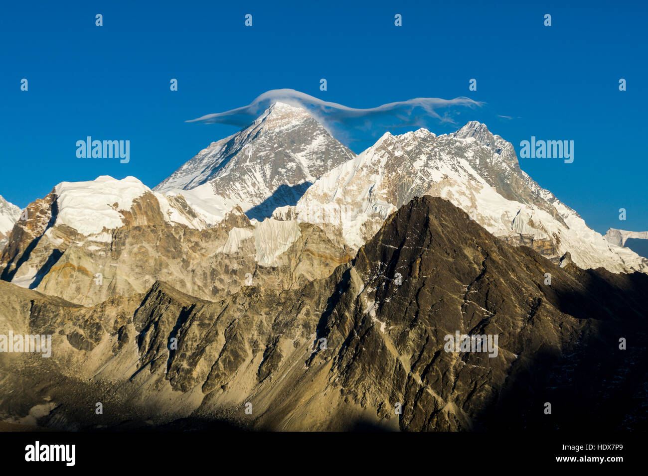 The mountain Mt. Everest (8848m) with a white cloud on top, seen from Gokyo Ri (5360m) at sunset - Stock Image