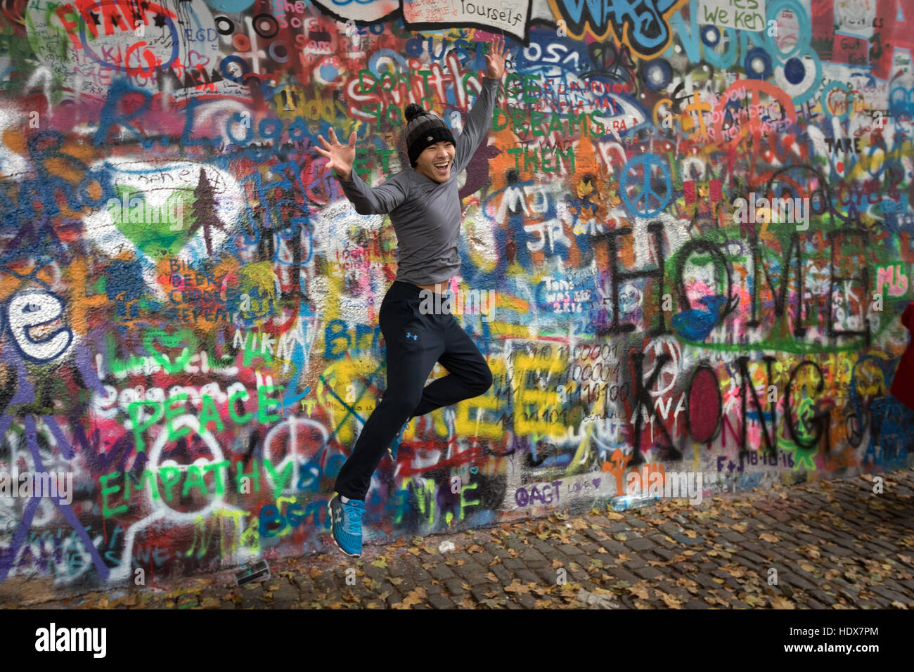 A young visitor leaps in front of the John Lennon Wall, in Malá Strana, Prague - Stock Image