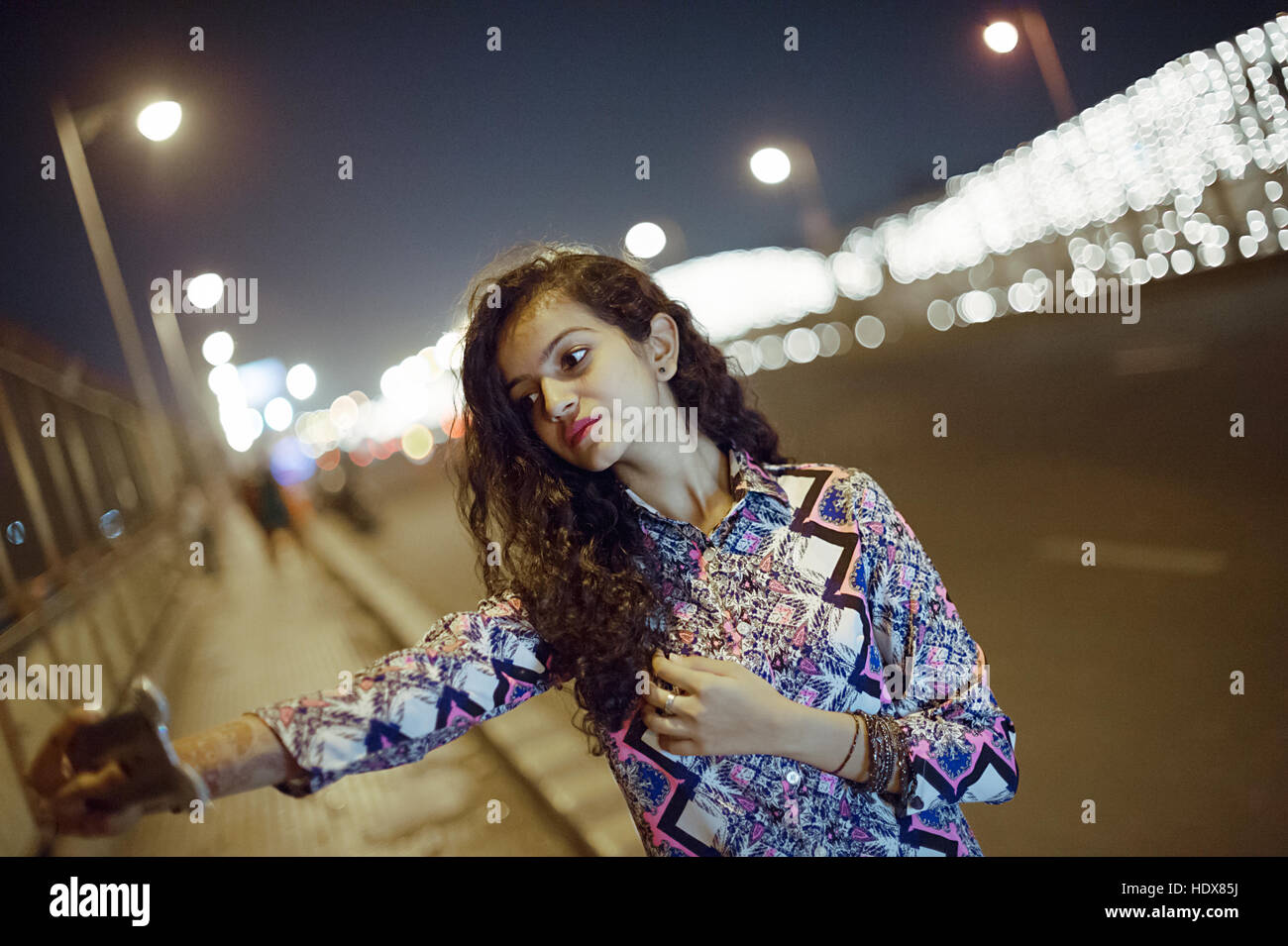 A young girl taking selfie on light decorated Ellis Bridge, Ahmedabad, India on Diwali festival with bokeh at evening - Stock Image