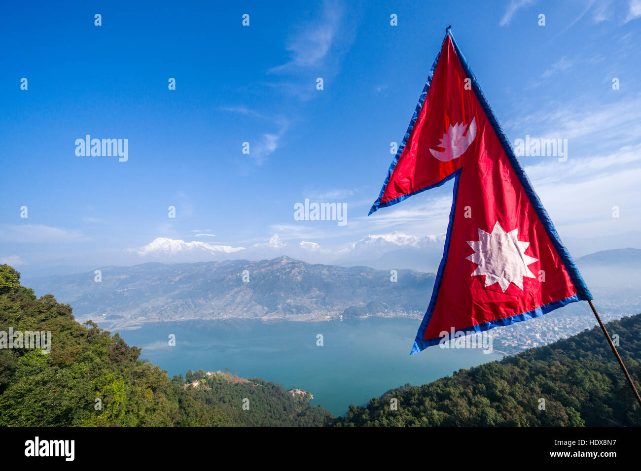 The nepali national flag is weaving high above the Phewa Lake and Pokhara, Annapurna mountains in the distance Stock Photo