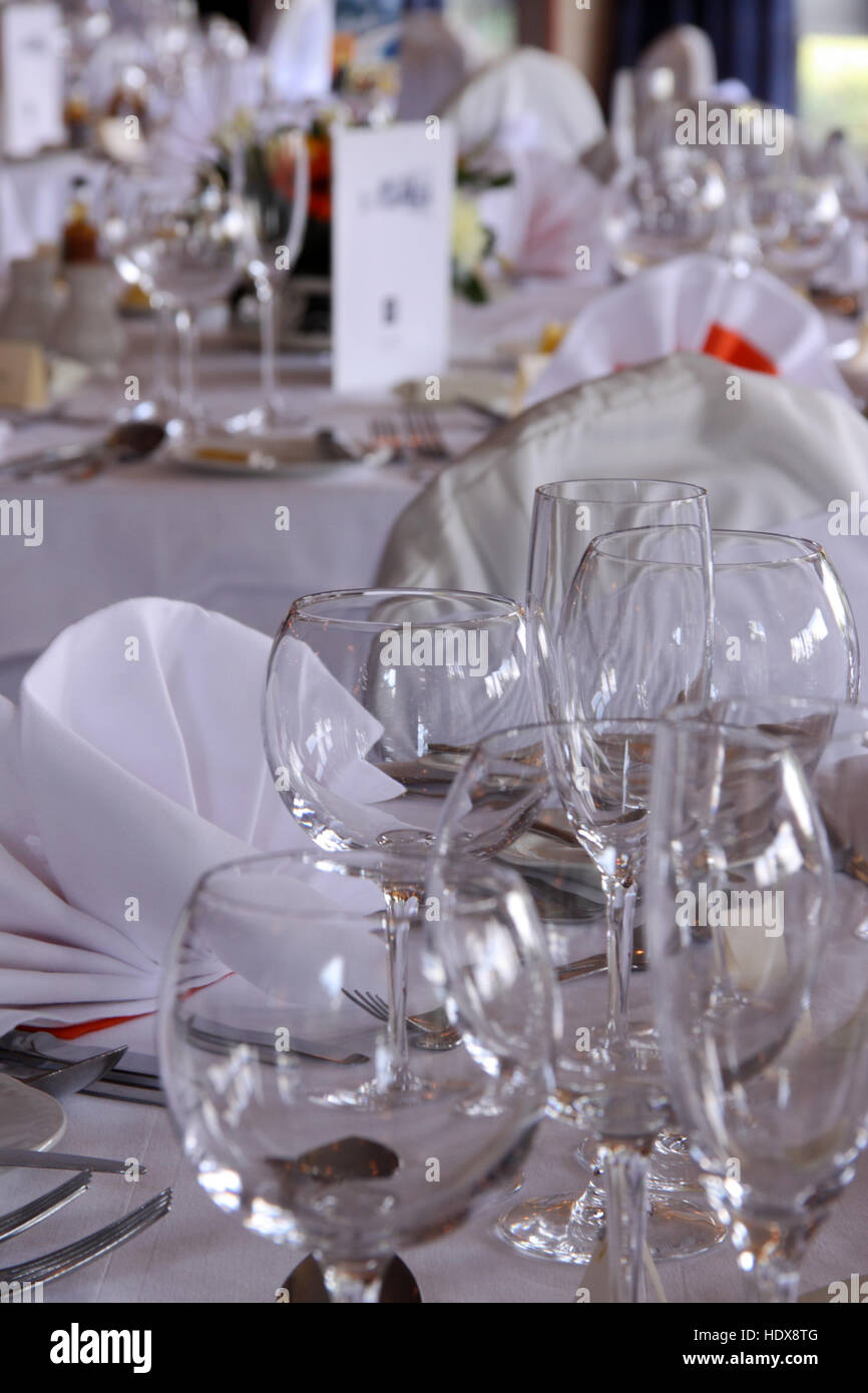 Table laid for a wedding breakfast reception, glasses, white linen, cutlery, crockery - Stock Image