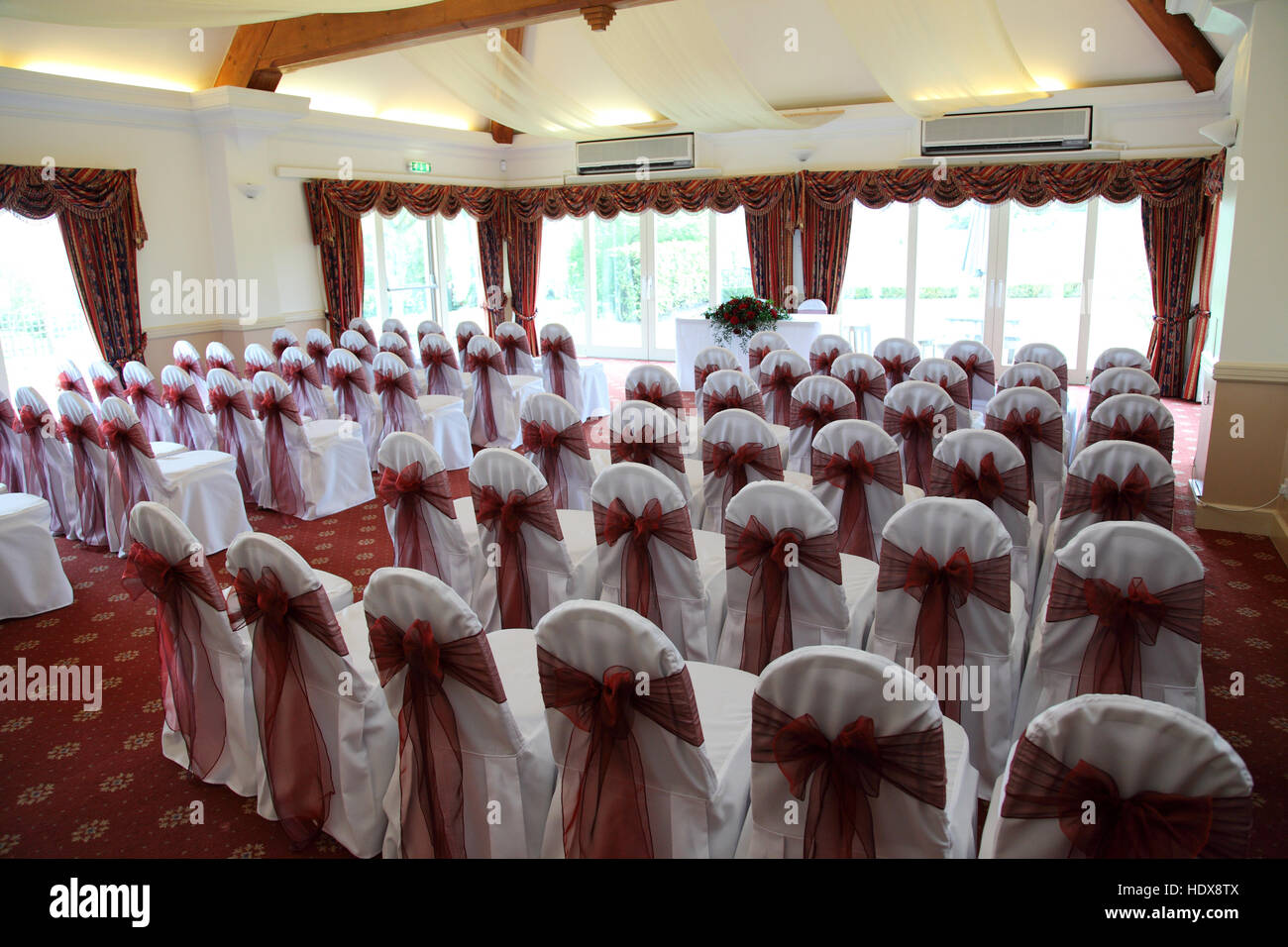 A room laid ready for a civil wedding ceremony, chairs with white covers, and tied with dark pink bows - Stock Image