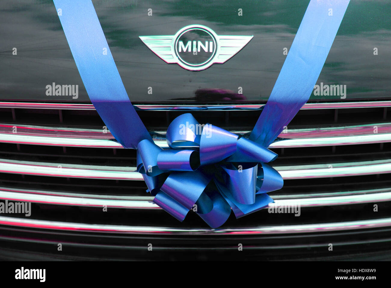 BMW Mini used as a wedding car, tied with a blue ribbon and bow over the radiator grill. - Stock Image