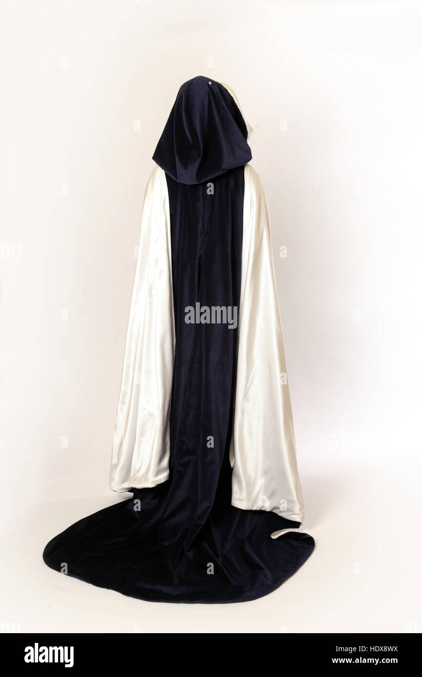 A ladies navy blue velvet cloak with a hood, lined with silk, shown from behind - Stock Image