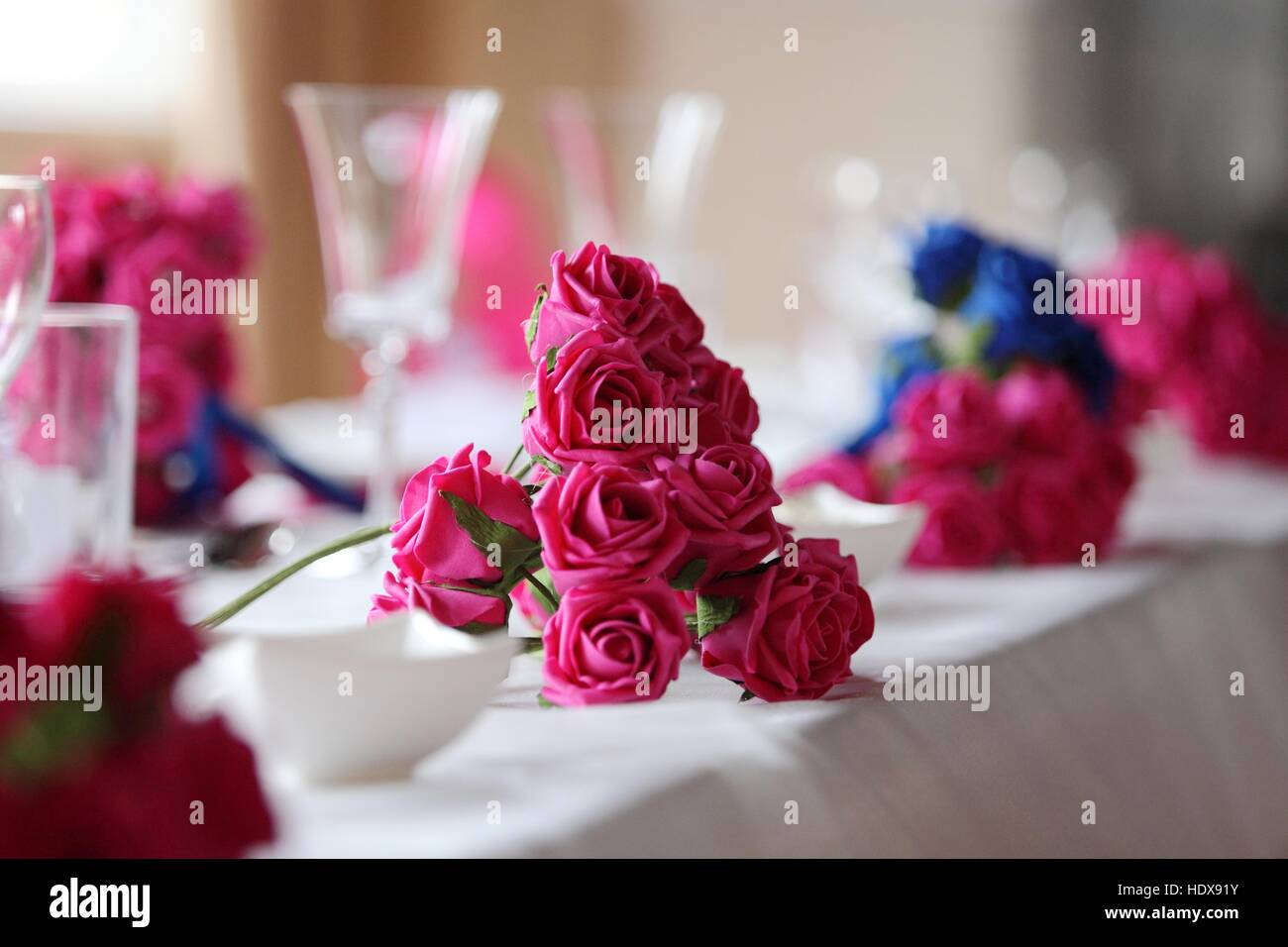 Wedding breakfast table laid ready for use with pink and blue silk flower arrangements, cutlery, crockery, glasses, - Stock Image