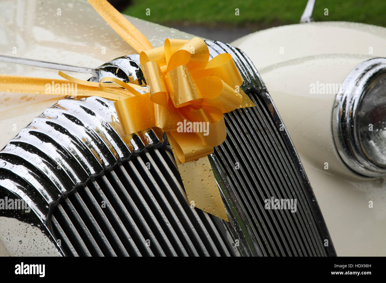 Vintage wedding car with a yellow ribbon tied in a bow on the radiator grill, and covered in rain spots. Stock Photo