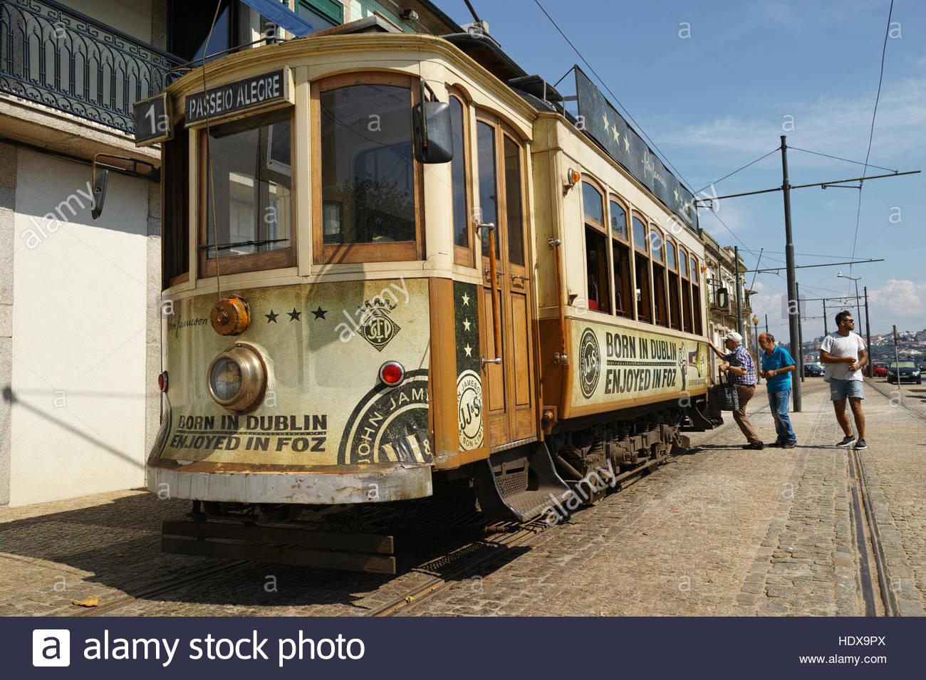 People boarding tram 1 at Passeio Allegre the stop for Foz do Douro: Porto, Portugal. - Stock Image